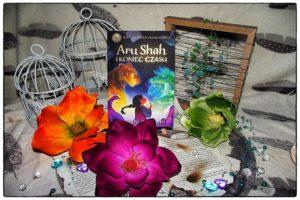 Stojący egzemplarz powieści Aru Shah i koniec czasu w otoczeniu kwiatów i dwóch ozdobnych klatek